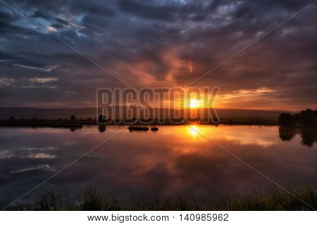 stunning spring sunset scene at Rotbav (called the delta area from the Carpathians) lake near Brasov. Romania. Low key, dark background, spot lighting, and rich Old Masters