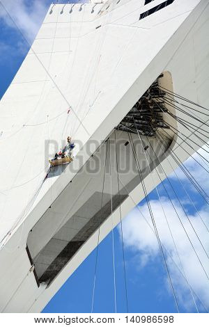 MONTREAL CANADA JULY 30 2016. Men repair the Montreal Olympic Stadium  tower. It's the tallest inclined tower in the world.Tour Olympique stands 175 meters tall and at a 45-degree angle