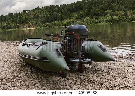 the green boat of pvc with the water-jet engine on the river bank