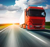 Red truck on blurry asphalt road over blue cloudy sky background poster