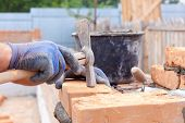 Construction mason worker bricklayer installing red brick with trowel putty knife outdoors poster