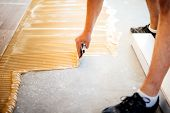industrial worker adding glue on cement floor preparing surface for wood parquet poster