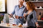 Look here. Handsome man showing a photo on the tablet to his beautiful wife who looking at it with interest while having breakfast in the morning poster