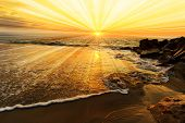 Ocean sunset sun rays is a colourful ocean scenic with sun beams bursting forth from the sun in a vivid surreal seascape. poster