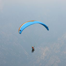 Paraglider flying over mountains at Lake Garda (Italy)