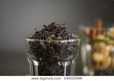 Extreme close up of finest quality Indian tea powder in a glass along with fresh spices or Masala in the background.