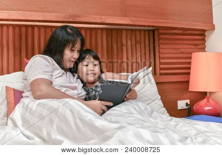 Family Reading Bedtime. Young Mother Reading A Book To Her Daughter. Happy Time In Bedroom