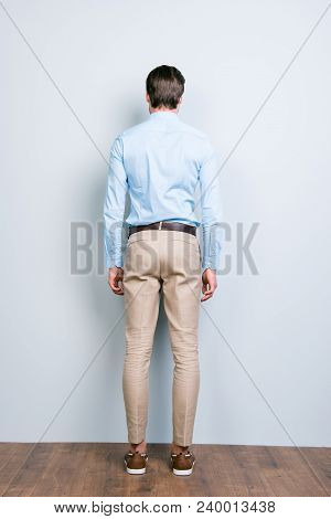 Full Length Back View Of A Man Standing Close To Grey  Wall, Wearing Formalwear, Shirt, Pants
