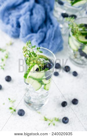 Detox Infused Flavored Water With Blueberry, Cucumber And Thyme On White Background. Refreshing Summ