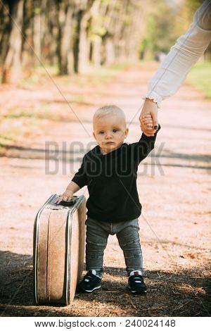 Travelling Child Carry Suitcase On Natural Landscape. Travelling Baby Boy Travel With Vintage Bag Wi