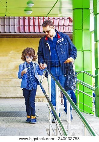 Dad And Son Go Out Of The Store With A Purchase Checking The Cash Receipt. The Father Teaches His Li