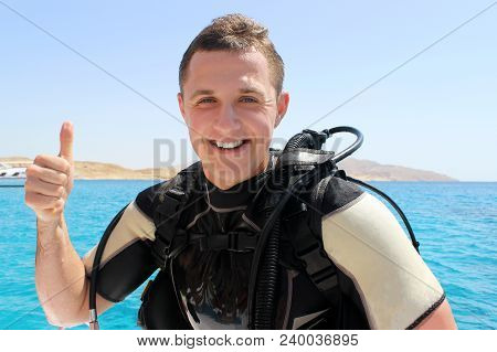 Happy Diver In A Suit For Diving Shows Trumb Up After Diving.