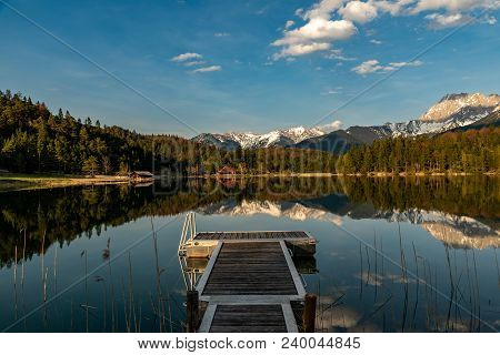 A View To The Alps With Great Reflections With A Footbridge In Front
