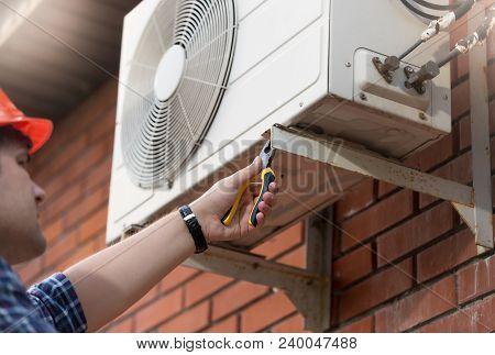 Closeup Photo Of Male Worker Installing Air Conditioner Unit
