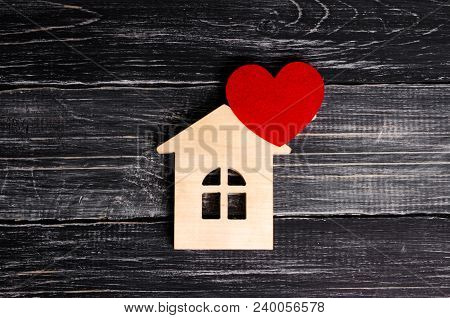 Wooden House With A Red Heart On A Background Of Black Wooden Boards. A Notification Icon For The Ap