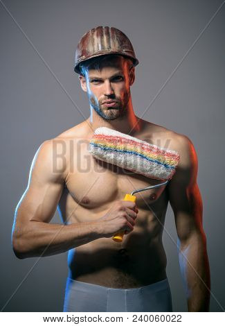 Handsome Worker With Paint Roller. Painter Man. Muscular Painter Man Holding Paint Roller. Professio
