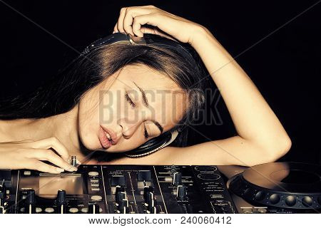 Portrait Of Young Beautiful Sexy Disk Jockey Girl In Headphones Lying With Closed Eyes On Profession