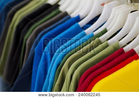 Colorful T-shirts On Hang For Sale In Shop. Multicolored Summer Top On Hanger. Summer Season Clothes