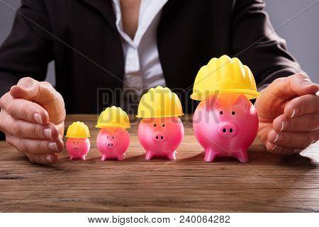 Businessperson Protecting Piggybanks With Yellow Hardhat