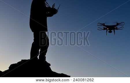 Man Operating A Drone At Sunrise;media Sector