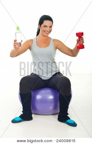 Happy Sportswoman Giving Water And Barbell