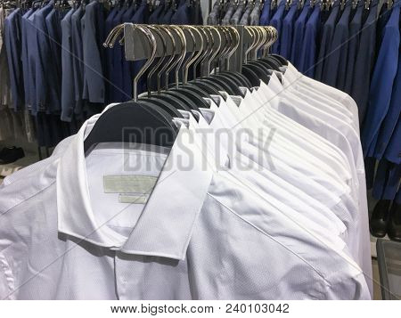 Clothes hang on a shelf . Cloth Hangers with d Shirt, suits. Men's business clothes