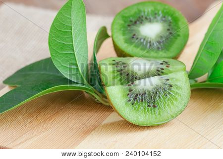 Fresh And Juicy Kiwi Fruit And A Piece On Cutting Board. Ripe Kiwi Fruits On Wood Table In Side View