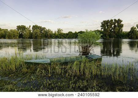 Lonely Fisherman's Boat Floating On Calm Lake Water.