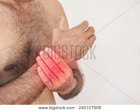 Unhappy Man Suffering From Pain In Hand On White Background. Healthcare And Medical Concept.