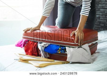 Travel And Vacation Concept, Happiness Young Woman Packing A Lot Of Her Clothes And Stuff Into Suitc