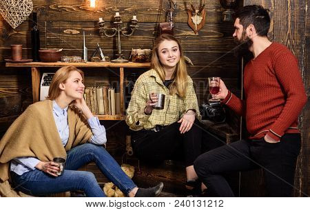 Family enjoy conversation in gamekeepers house. Friends, family spend pleasant evening, interior background. Sincere conversation concept. Girls and man on happy faces hold metallic mugs, talking. poster