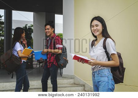 Young Asian Woman Student And Friends Are Tutoring Exam With Study Book And Laptop In Back Side, Stu
