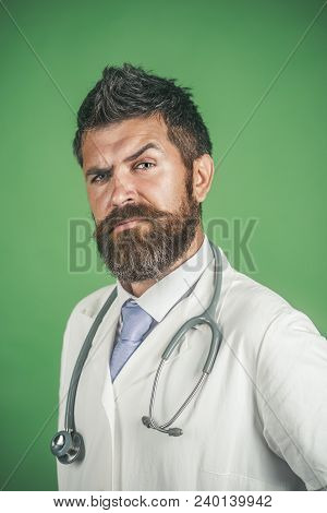 Handsome Serious Doctor In White Coat And Stethoscope On Neck. Serious Bearded Intern, Physician, Do
