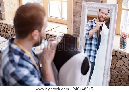 My Work. Attractive Male Couturier Modifying Dress While Smiling To Mirror