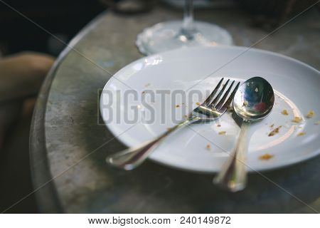 Eat Completely Empty Dish On Stone Table. Fork And Spoon In Plate After Finish Eat Food. Concept Of