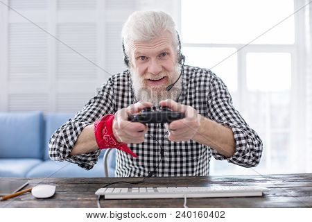 Convenient Equipment. Upbeat Elderly Man Sitting At The Table And Using A Game Controller While Play