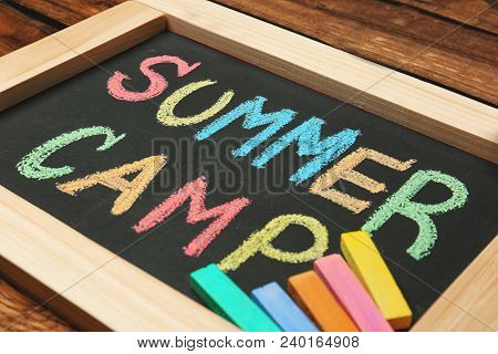 Little Blackboard With Text Summer Camp Chalked In Different Colors On Table
