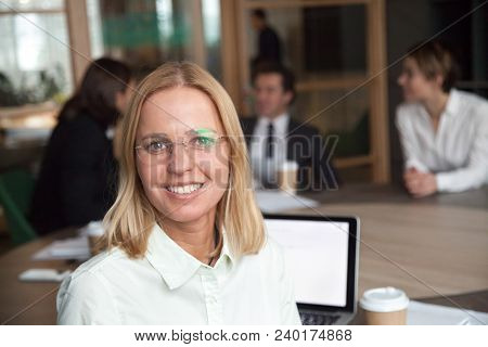 Smiling Middle-aged Businesswoman Looking At Camera At Group Meeting, Friendly Female Company Execut