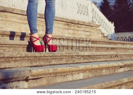 Woman Wearing Blue Jeans And Red High Heel Shoes In Old Town. The Women Wear High Heels Standing On