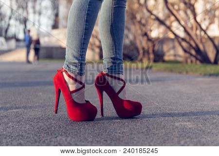Woman Wearing Blue Jeans And Red High Heel Shoes. The Women Wear High Heels Standing On The Road. Se