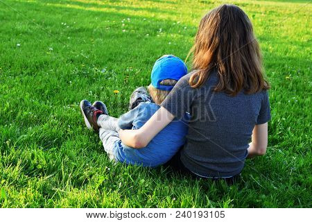 Teenage Girl And Her Two Years Old Little Brother Sitting In Green Meadow Grass And Waiting For Suns