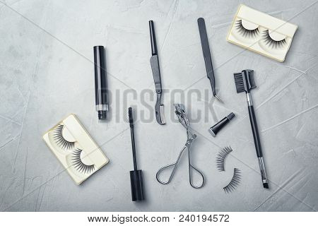 Flat Lay Composition With False Eyelashes And Cosmetic Tools On Grey Background