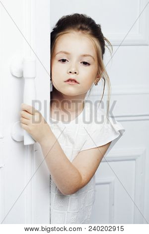 Children's fashion. Beautiful pensive serious blonde girl in white clothes. Fashion, lifestyle and people concept.