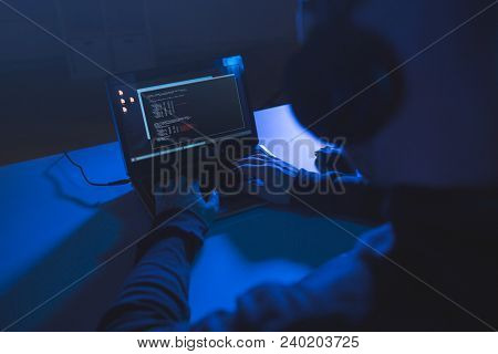 cybercrime, hacking and technology concept - male hacker with headphones and coding on laptop computer screen wiretapping or using virus program for cyber attack in dark room