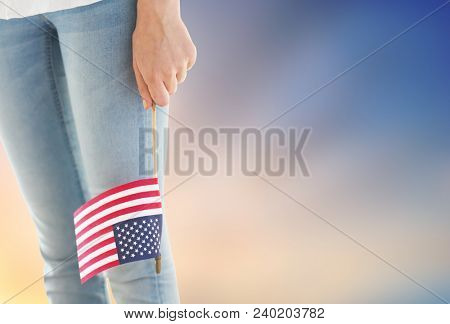 independence day, celebration, patriotism and holidays concept - close up of woman legs and hand holding american flag at 4th july party over evening sky background