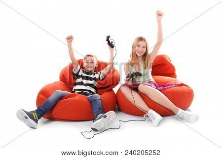 Happy children with video game controllers on white background