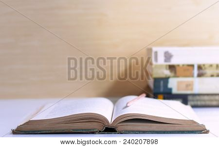 Open Hardback And Textbook Stacked On The Table On Brown Wall Background. The Concept Of Intelligenc