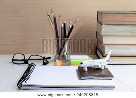 Plan To Travel Or Study Abroad. Open Notebook With Passport, Glasses, And Stationary Placed On The T