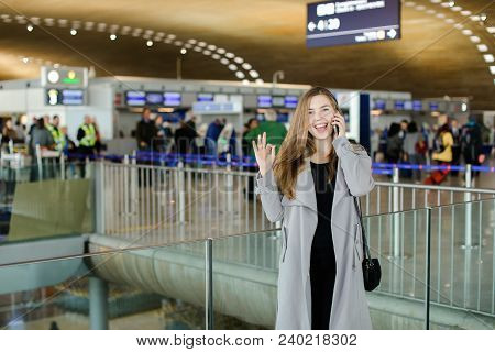 Girl Talking By Smartphone At Airport Hall, Wearing Grey Coat And Black Bag And Showing Ok. Concept
