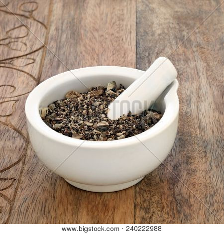 Comfrey root herb used in alternative and chinese herbal medicine, is used as a skin care salve and can treat skin ailments. In a mortar with pestle on rustic wood background. Symphytum officinale.